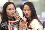 香港單車隊昨凱旋,拍大合照時李慧詩(左)與師妹馬詠茹(右)親吻攜手取得的團體爭先賽銀牌。(賴俊傑攝)