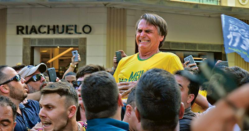 巴西總統候選人波索納羅在競選集會遭捅刺後,痛苦地掩住腹部。(法新社)