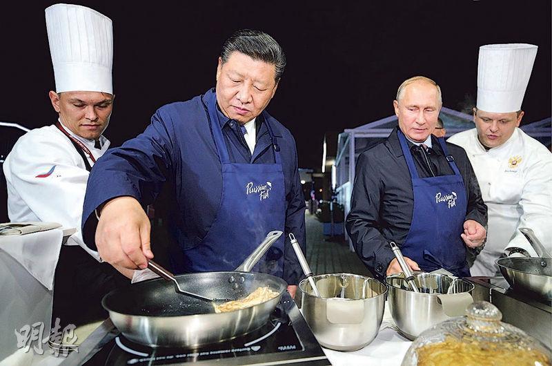 俄羅斯總統普京(前右)和中國國家主席習近平(前左)昨日在符拉迪沃斯托克東部經濟論壇期間參觀「遠東街」展覽時同做魚子醬煎餅。(法新社)
