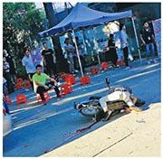 疑兇(遠處黃衫坐者)斬死工友後沒有逃跑,坐在一旁等警察到來。(網上圖片)