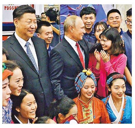 圖為習近平(左)與普京同在「海洋」全俄兒童中心學習休養的中國兒童合影。(網上圖片)