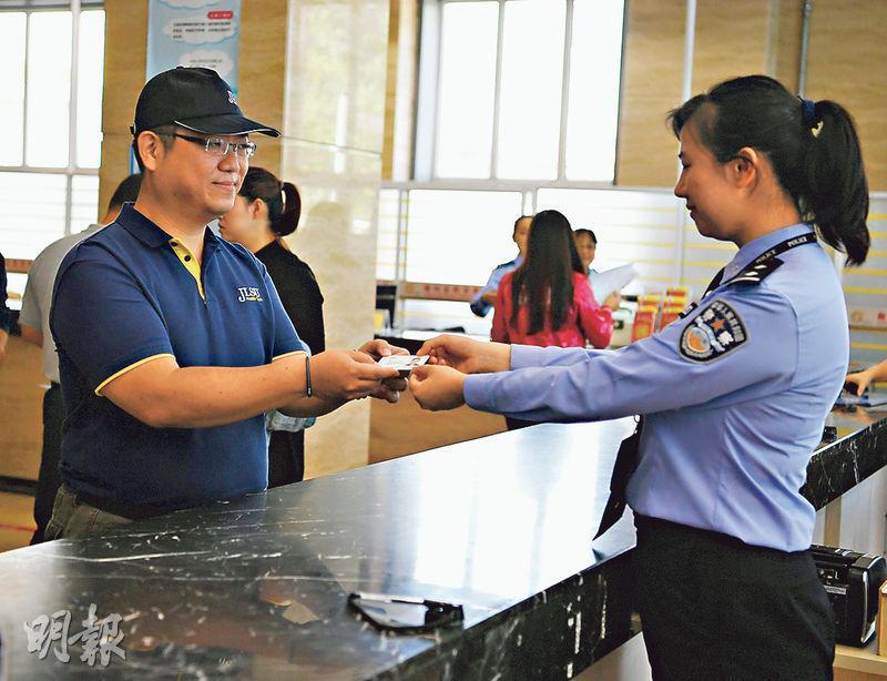 一台灣人在首發式領取台灣居民居住證。(中新社)