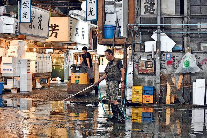 東京築地魚市場下月搬遷,市場內數以萬計老鼠恐群起四竄,政府人員正致力滅鼠。圖為一名工人本月初在築地市場內洗地。(法新社)
