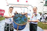 陽澄湖大閘蟹今年大豐收,圖為兩名嘉賓昨日在開捕儀式上舉起一籮蟹。(網上圖片)