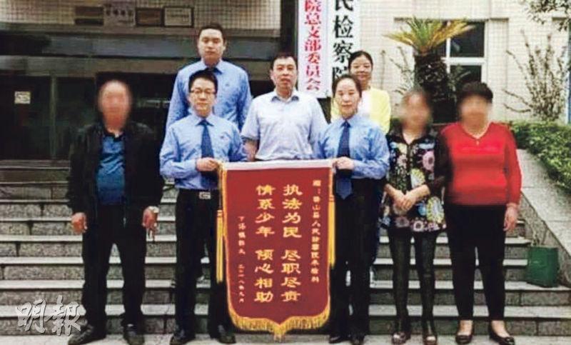 涉強姦男生獲准保釋返校後,其家長向檢方送上錦旗並與之合影(圖)。(網上圖片)