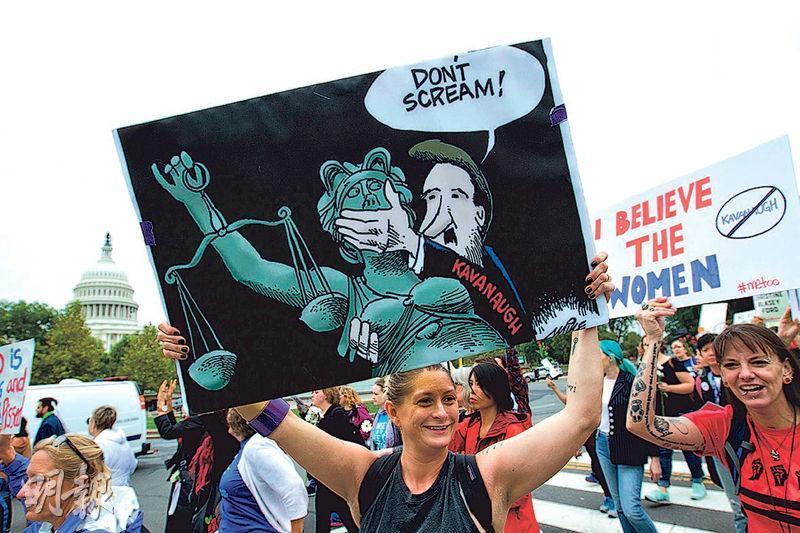 周四在國會山莊外有民眾參與反對卡瓦諾獲提名為最高法院大法官,示威者舉起畫像,當中象徵司法公義的正義女神肖像遭封口。(法新社)