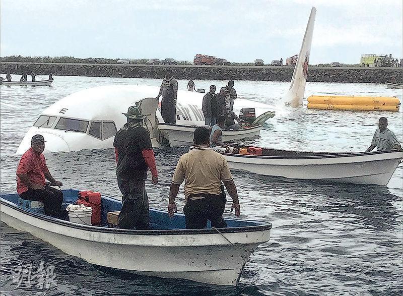 客機墜海後,機身一半浸於水中。(法新社)
