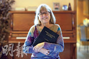 加拿大滑鐵盧大學物理與天文系副教授斯特里克蘭(圖)是近55年來首名女性獲諾貝爾物理學獎。她昨得悉獲獎之後,在安大略省滑鐵盧的家中捧着30年前的論文拍照。(路透社)
