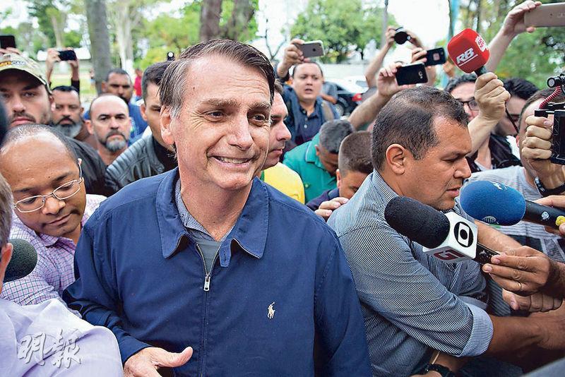 有「巴西特朗普」之稱的博爾索納羅(中)周日在里約熱內盧投票後,被傳媒追訪。(法新社)