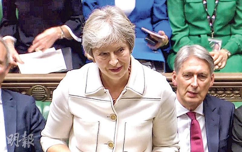 英國首相文翠珊(前)周一在下議院匯報脫歐談判進展。(法新社)