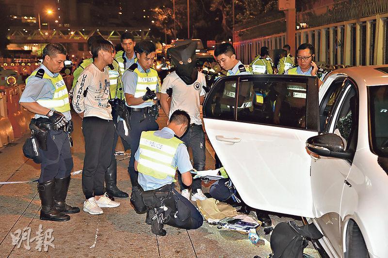 警方在彩虹道爵祿街交界截停白色福士,拘捕司機(戴頭套者)及一名男乘客(左二)並在現場蒐證。(蔡方山攝)