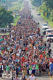 來自中美洲的大批難民周日在墨西哥城市塔帕丘拉的高速公路上前進,向美國邊境進發。(路透社)