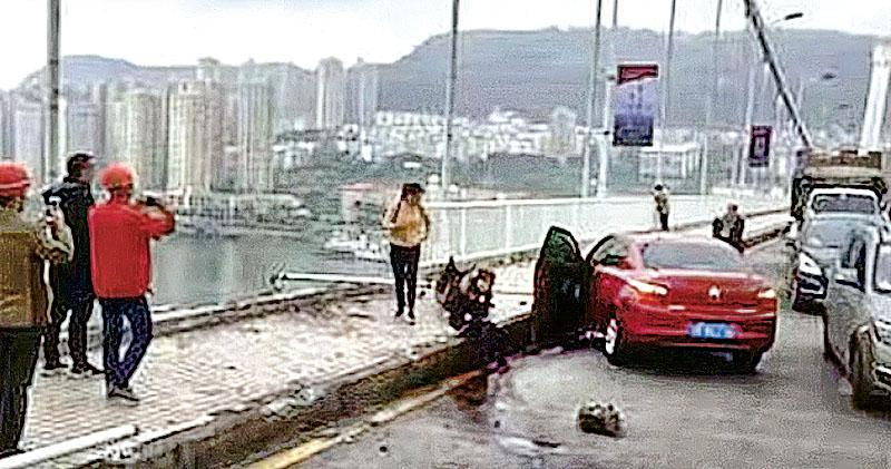 巴士在萬州長江二橋上突然越過對面行車線,與一輛私家車相撞後,撞斷護欄墜入江中,現場可見橋上已失去一段護欄,而鄺姓私家車女司機則坐在路邊等待救援。(網上圖片)