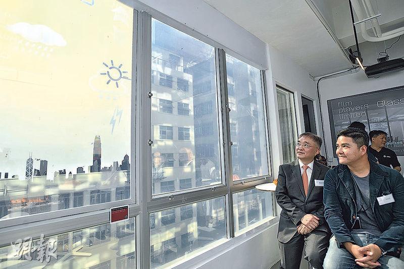 智能顯示電膜貼於玻璃窗上可化成顯示器。信和集團創新聯席董事楊孟璋(左)及Film Players Limited行政總裁蘇德政(右)昨在研發室內,示範電膜的天氣狀况顯示功能。(楊柏賢攝)