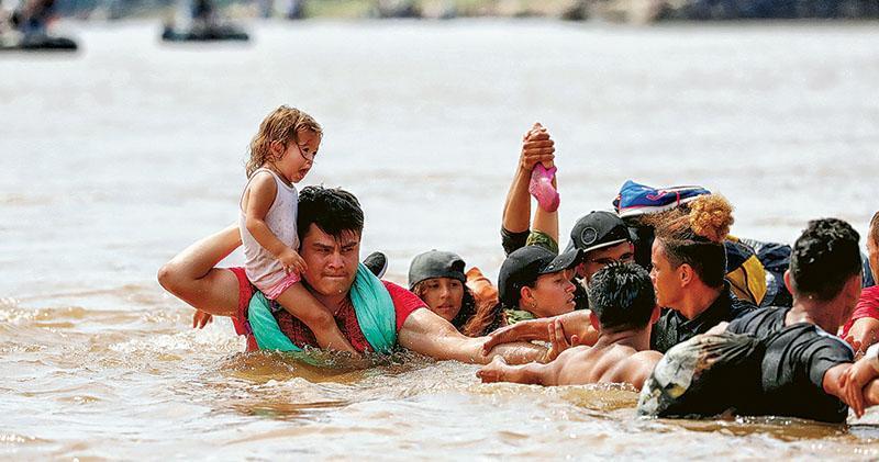 偷渡者周一從危地馬拉特昆烏曼(Tecun Uman)組成人鏈,互相協助渡過跨境大河入墨西哥,有人肩托着孩子。(路透社)