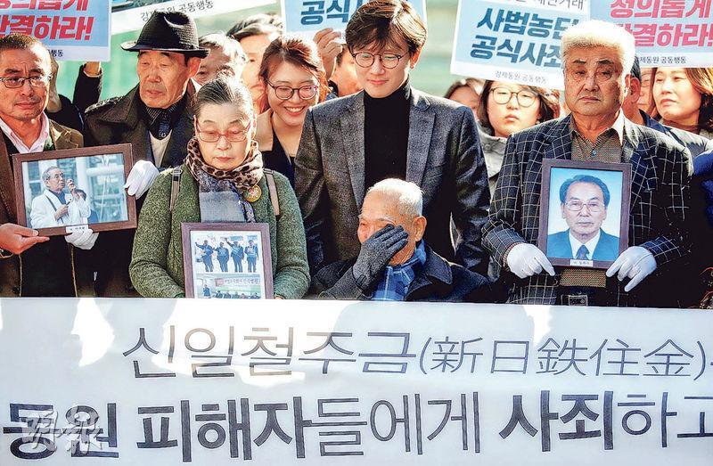 追究日本在二戰年代強徵奴役的九旬老翁李春植(前右二坐者)在勝訴後拭淚。其身旁人士捧着照片者則代表另外3個已辭世的原告。(路透社)