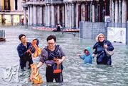 意大利多地降暴雨,威尼斯聖馬可廣場周一被水淹浸,人們要涉水而行。(路透社)