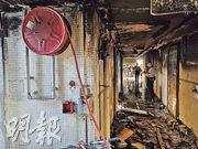 上水天平邨天賀樓15樓一單位,昨凌晨發生爆炸及起火案,起火樓層的住戶指曾在走廊敲碎火警鐘玻璃,但無法啟動警鐘,拉出的消防喉水力不足,形容「只有幾滴水滴出來」。大廈解封後,探員再到上址調查,可見全層走廊牆身嚴重熏黑。(林智傑攝)