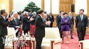 國家主席習近平(右)昨日在北京接見香港澳門各界慶祝國家改革開放40周年訪問團,他步入會場時獲與會者拍掌歡迎,而率領香港訪京團的特首林鄭月娥(紫衣者)則與澳門特首崔世安(習背後), 以及國務院副總理韓正(林太背後)等中央領導人一同步入會場。(新華社)