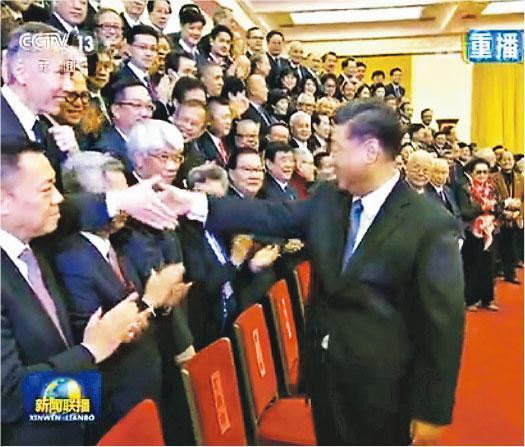 央視新聞聯播昨晚播出國家主席習近平會見訪京團的報道,畫面可見習在大合照前與部分團員握手。圖為習與站在第二排的信和置業主席黃志祥(左)握手。(央視撮圖)