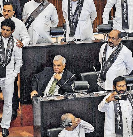 斯里蘭卡前任總理維克勒馬辛哈(中)昨天出席國會,其統一國民黨籍議員以起立方式,表決贊成不信任新總理拉賈帕克薩的動議。(法新社)
