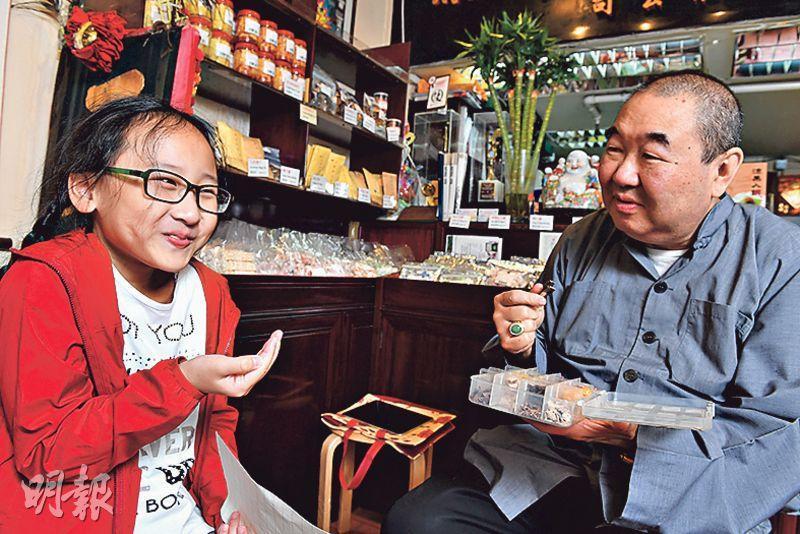 王柏源(右)拿出一盒蜜餞給鍾妤(左)試吃,她首先放進嘴裏的是佛手瓜脯,酸得皺起眉頭呢!