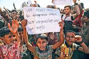 在孟加拉Unchiprang難民營抗議的羅興亞難民中有不少兒童,一名男孩舉起「沒有公民身分及權利,我們永不會回緬甸」的標語。(路透社)