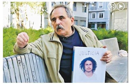 西班牙青年羅德里格斯因用維他命等「另類藥物」治療血癌而喪命,其父手持他的肖像抱不平。(網上圖片)