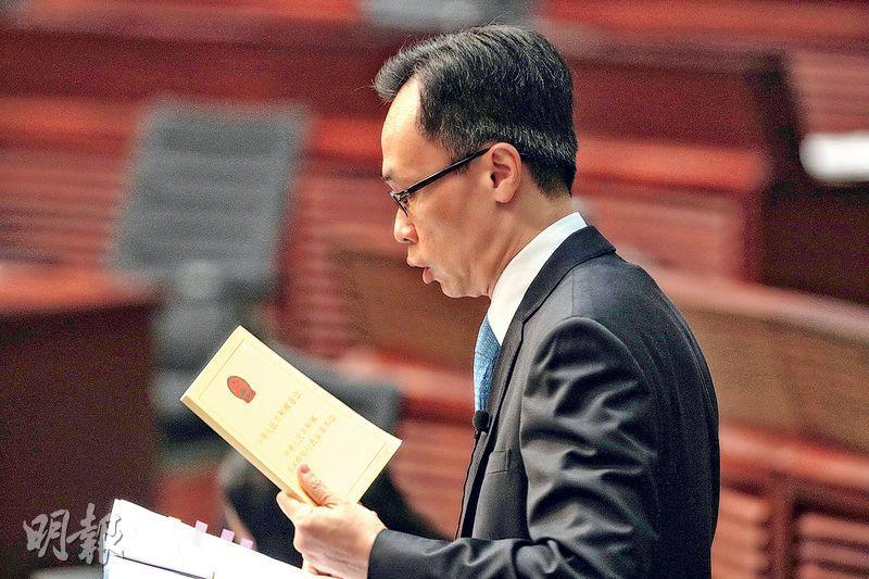 政制及內地事務局長聶德權(圖)手執新近印製、加入了國家憲法內容的《基本法》,明顯較舊版厚。(曾憲宗攝)