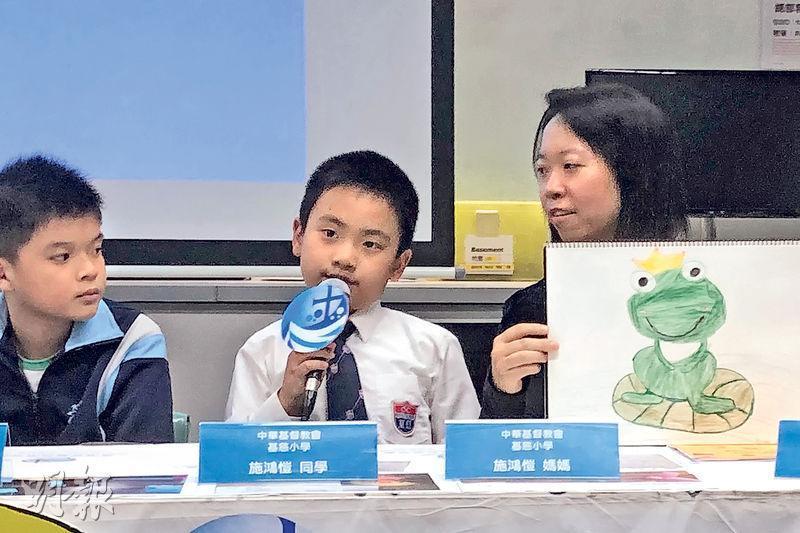 中華基督教會基慈小學小三生施鴻愷(中)說,小二時自己視藝科成績稍遜,故今年復活節訂下目標,盼在假期創作畫冊,並參考了《伊索寓言》,畫出其母(右)手中的青蛙圖畫。媽媽說,鴻愷繪畫的青蛙有不同表情,認為他可透過繪畫表達情感。(劉家豪攝)