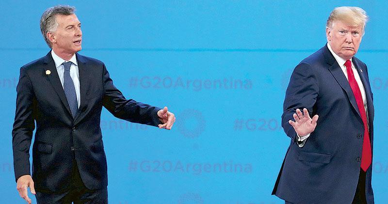 上周五在原定拍攝20國集團領袖團體照的場地,美國總統特朗普(右)一度自顧自舉步離開,令阿根廷總統馬克里(左)頗為尷尬。(路透社)