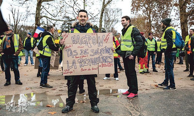 42歲的巴黎失業電腦技術員Idir Ghanes舉牌參加示威,指總統馬克龍拿不出解決社會問題的方案,因此人民要革命。(網上圖片)