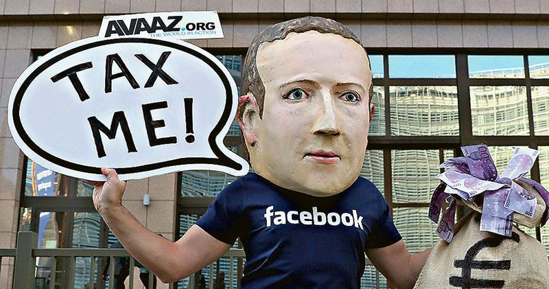 圖為民眾戴上朱克伯格的頭套,周二到比利時布魯塞爾歐盟總部外示威,舉起「向我徵稅」的示威牌。(路透社)