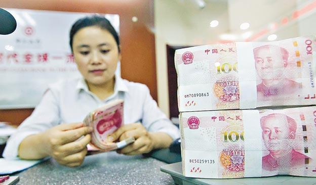 中國一間銀行的工作人員在點算貨幣。(中新社)