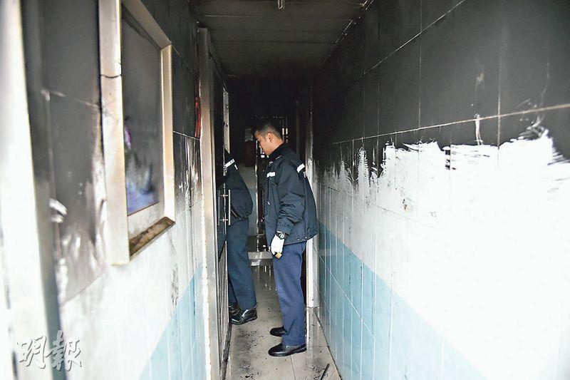 起火單位外走廊熏黑,走廊闊度僅約3呎,火警時因有男子倒臥頂着,住客未能推閘離家逃生。(林智傑攝)