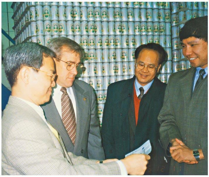 中國首個易拉罐生產商羅富昌(右二)與美國波爾公司的高層(左二)於1995年到青島啤酒廠房內檢查用罐情况。(受訪者提供)