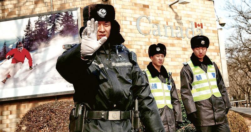 中國外交部昨證實,第3名在中國被捕的加拿大人因「非法就業」遭行政處罰。圖為昨日加拿大駐華大使館外有警員示意攝影師不要拍照。(路透社)