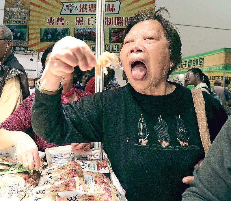 香港冬日美食節昨日冬至開幕,大批市民到場掃貨,不少商戶提供免費試食,攤檔外現人龍,食客急不及待把試食品放入口中。(李紹昌攝)