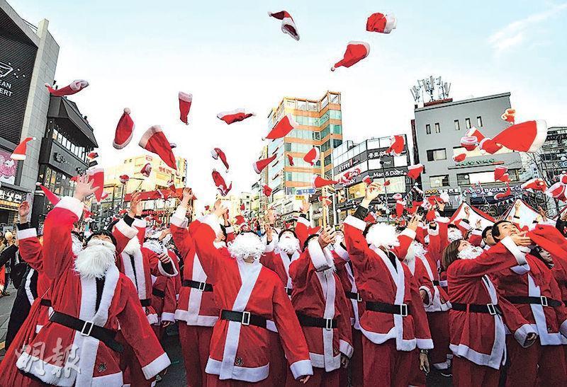 韓國一群義工裝扮成聖誕老人,周一平安夜在首爾市內給800個貧窮家庭的1200名孩子大派禮物,出發前他們把帽子拋到半空。(法新社)