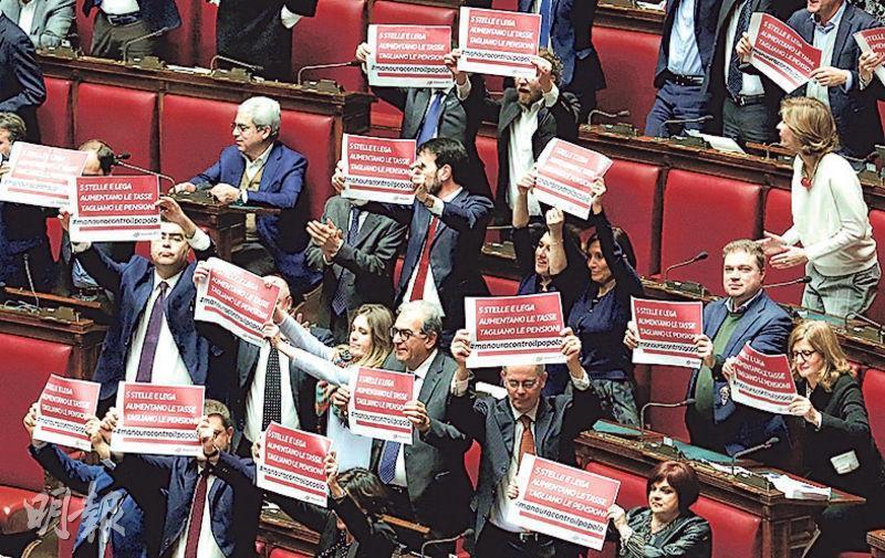 意大利眾議院上周六表決2019年度預算法案時,有議員舉牌抗議,斥政府加稅但減退休金。(路透社)