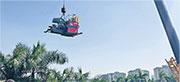 東莞台商陳昆鴻的工廠遭當地官員刁難不讓大貨車進入,工廠被迫用吊車把貨品從圍牆內吊出大馬路。(受訪者提供)