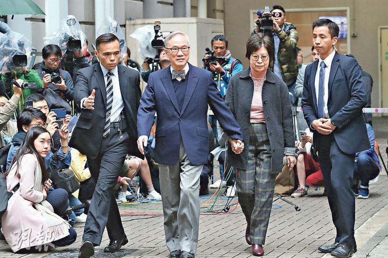 昨晨9時許,前特首曾蔭權(前左二)在G4陪同下,身穿一襲深藍色西裝、繫上藍白色格子煲呔,與太太十指緊扣離開瑪麗醫院羈留病房。(李紹昌攝)