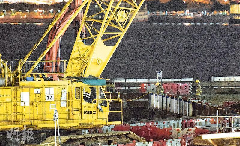 有工人於西九工地的天秤旁邊測試土壤時,發現泥土輻射超標,報案後消防及警方到場檢查。(蔡方山攝)