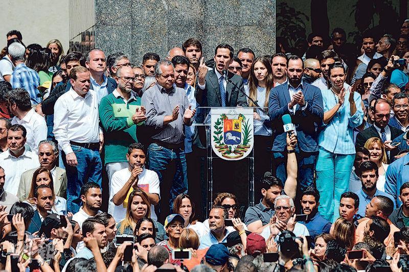 委內瑞拉國會議長瓜伊多(中)上周五向支持者發表演說,是他自我宣誓為臨時總統後首度公開亮相。(法新社)