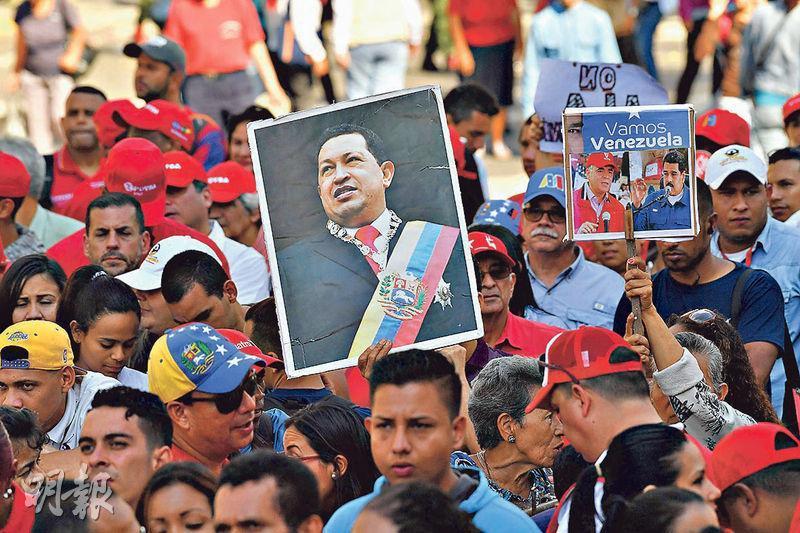 委內瑞拉國營石油公司職工周四在總統府外參加「反帝國主義者」遊行,支持總統馬杜羅,有人高舉已故總統查韋斯的照片。(法新社)