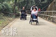電動輪椅使用者黃少川(左)參與制訂無障礙的行山路線時親身路試,如試用圖中香港仔水塘路段。黃指電動輪椅人士要留意電量,上落時減速;立法會議員張超雄及其需乘手推輪椅的女兒(右)亦同行路試,指出郊區斜路常見,張因年紀漸長,不時要與太太合力才能將輪椅推上斜,故提醒照顧者最好請同行人士幫忙。(湯曉津攝)