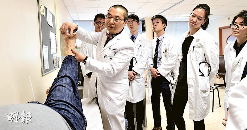 10名醫學生圍在門診的小病牀旁,看教授張德輝(前)示範為病人檢查身體。(賴俊傑攝)