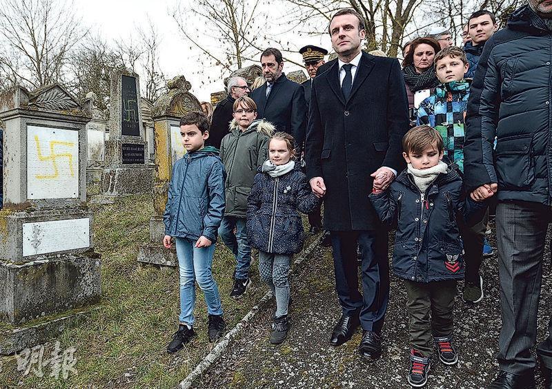 馬克龍周二到一個猶太墓園參觀,該猶太墓地遭人噴上納粹標誌。(路透社)