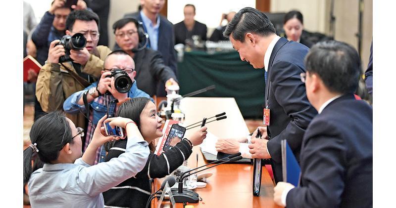 全國政協十三屆二次會議新聞發布會昨日在北京人民大會堂舉行,大會發言人郭衛民介紹有關情况並回答中外記者提問。圖為郭衛民在發布會結束後仍被記者追問。(新華社)