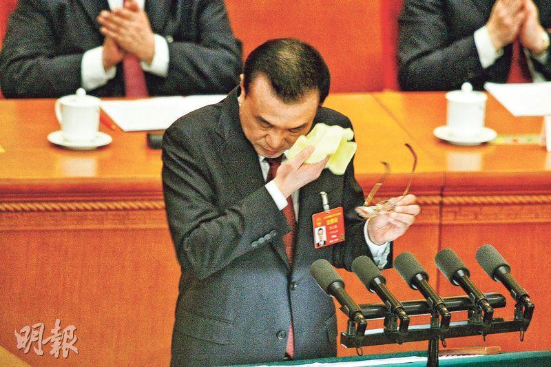 國務院總理李克強昨日作政府工作報告,他在宣讀報告時,似乎十分費力耗神,多次停下飲水並用毛巾抹汗。(鄭海龍攝)